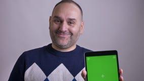 Close-upportret van de volwassen Kaukasische mens gebruikend de tablet en tonend het groene scherm aan camera het glimlachen stock videobeelden
