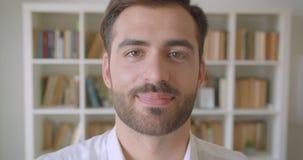 Close-upportret van de volwassen knappe gebaarde Kaukasische mens die camera bekijken die gelukkig in de bibliotheek glimlachen m stock footage