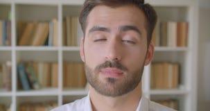 Close-upportret van de volwassen knappe Kaukasische mens die binnen camera bekijken die nadenkend in de bibliotheek zijn stock videobeelden