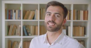 Close-upportret van de volwassen knappe Kaukasische mens die camera bekijken die cheerfully in de bibliotheek binnen glimlachen stock video