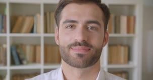 Close-upportret van de volwassen knappe Kaukasische mens die camera bekijken die gelukkig in de bibliotheek met boekenrekken glim stock videobeelden