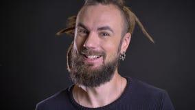 Close-upportret van de zonderlinge Kaukasische mens die positief vermaak en geluk op zwarte achtergrond tonen stock videobeelden
