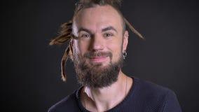 Close-upportret van de zonderlinge Kaukasische mens die positieve vermaak en glimlach op zwarte achtergrond tonen stock videobeelden