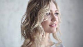 Close-upportret van een aantrekkelijk blonde jong meisje met een lichte samenstelling en krullen stock video
