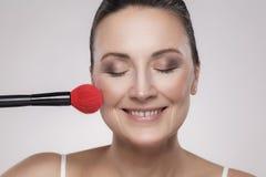 Close-upportret van een aantrekkelijke midden oude vrouw die met perfecte huid make-up met een rode borstel en toothy glimlach to stock foto's