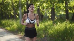 Close-upportret van een atleet Het meisje die langs de weg bij zonsondergang lopen Jonge vrouw die sporten in aard doen langzaam stock video