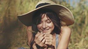 Close-upportret van een charmant jong meisje in een strohoed Een meisje met ongebruikelijke ogen bekijkt en glimlacht bij de came stock videobeelden