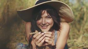 Close-upportret van een dorpsmeisje in een strohoed met een stro in haar handen Een leuk meisje glimlacht en bekijkt de camera stock video