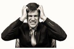 Close-upportret van een gefrustreerde zakenman die zijn haar trekken stock foto
