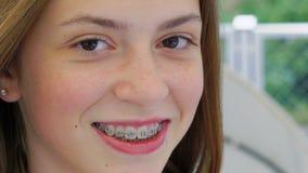 Close-upportret van een gelukkig meisje die bij camera glimlachen langzaam stock videobeelden