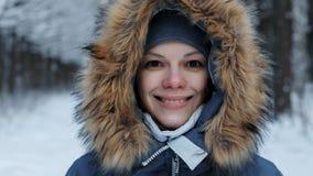Close-upportret van een glimlachende vrouw in een hoodie met bont op de straat stock video