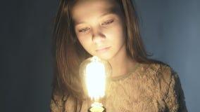 Close-upportret van een jong meisje die een gloeiende gloeilamp in haar handen houden stock videobeelden