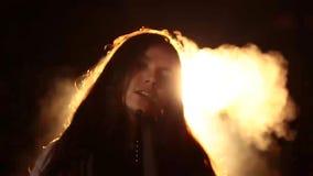 Close-upportret van een jonge bruin-haired vrouw, sexy rokende waterpijp op een donkere Studio als achtergrond rook zoals brand d stock video
