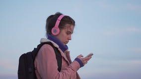 Close-upportret van een jonge vrouw die zich op het strand met een smartphone bij zonsondergang bevinden stock footage