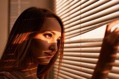 Close-upportret van een meisje dat uit het venster door de zonneblinden in het warme licht van de het plaatsen zon kijkt stock foto's