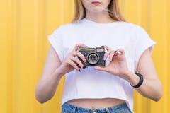 Close-upportret van een meisje met een oude retro camera in haar wapens stock fotografie