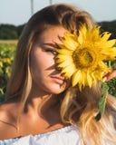 Close-upportret van een meisje met een zonnebloem Royalty-vrije Stock Afbeeldingen