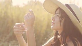 Close-upportret van een meisjeszitting op een weide en het genieten van een van warme zonsondergangzon stock videobeelden