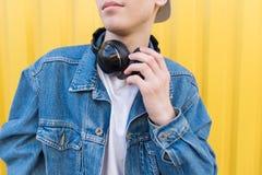 Close-upportret van een mens in een denimjasje en een draadloze hoofdtelefoon op de hals royalty-vrije stock foto