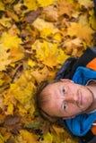 Close-upportret van een mens die op gevallen de herfstbladeren liggen Royalty-vrije Stock Foto's