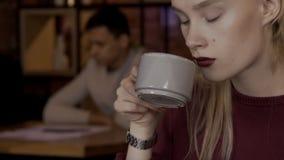 Close-upportret van een mooie blondevrouw die thee in een koffie drinkt stock video