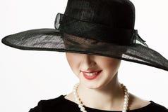 Close-upportret van een mooie vrouw in een zwarte hoed in retro s Stock Fotografie