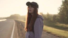 Close-upportret van een roodharig meisje met het doordringen in haar neus en lippen en hoofdtelefoons Op de zonsondergang Langzam stock videobeelden