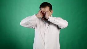 Close-upportret van een schreeuwende mens Een jonge zakenman sluit zijn pijnlijke ogen met scheuren op groene achtergrond stock video