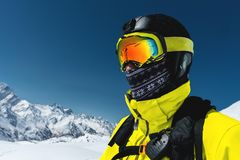 Close-upportret van een skiër in een masker en helm met een gesloten gezicht tegen een achtergrond van snow-capped bergen en stock afbeelding