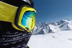 Close-upportret van een skiër in een masker en helm met een gesloten gezicht tegen een achtergrond van snow-capped bergen en stock fotografie