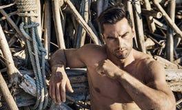 Close-upportret van een spiermens die op een strandzand liggen royalty-vrije stock fotografie