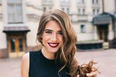 Close-upportret van efficiënt meisje met lang krullend haar die aan camera op straat bij de bouw van achtergrond glimlachen Zij d royalty-vrije stock foto