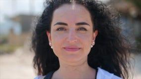 Close-upportret van Europese Mooie Leuke Donkerbruine Jonge Vrouw of Vrolijk Meisje die in de Camera, Blazende Wind kijken stock video