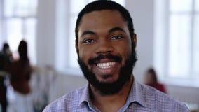 Close-upportret van gelukkig positief die Afrikaanse managerzakenman met baard glimlachen op modern kantoor Gezonde werkplaats stock videobeelden