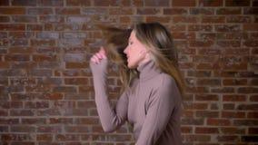 Close-upportret van gelukkige aanbiddelijke mooie vrouw die van het Kaukasische behoren tot een bepaald ras met de bakstenen muur stock video