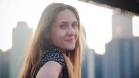 Close-upportret van gelukkige speelse schuwe Europese vrouw die met lang haar bij camera bij de horizon van de de stadsbrug van M stock footage