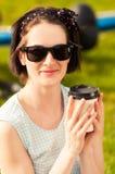 Close-upportret van gelukkige vrouw met zonnebril en koffie Stock Afbeeldingen