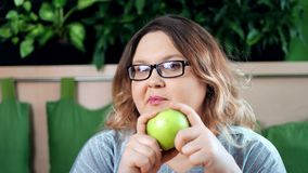 Close-upportret van glimlachende op dieet zijnde vette vrouw die verse groene appel bijten die camera bekijken stock video