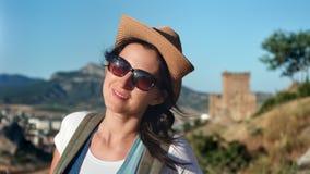 Close-upportret van glimlachende vrouwelijke toerist in hoed en zonnebril die van vakantie genieten bij zonsondergang stock videobeelden