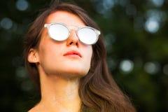 Close-upportret van glorierijke jonge vrouw in posin van spiegelglazen Stock Foto