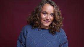 Close-upportret van het aantrekkelijke Kaukasische vrouwelijke schuw en pijnlijk worden terwijl het glimlachen en het bekijken ca stock video