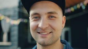 Close-upportret van het aantrekkelijke volwassen mens glimlachen die zich in openlucht in straat bevinden stock videobeelden