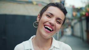 Close-upportret van het blije meisje lachen die camera in openlucht in straat bekijken stock footage