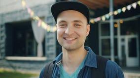 Close-upportret van het blije student glimlachen die in openlucht in stadsstraat lachen stock video