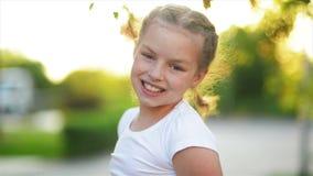 Close-upportret van het blonde Europese meisje glimlachen met al haar tanden Het gelukkige jonge geitje in zonnige middag maakt e stock footage