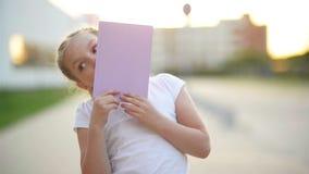 Close-upportret van het blonde Europese meisje glimlachen met al haar tanden Het gelukkige jonge geitje in zonnige middag maakt e stock videobeelden