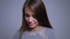 Close-upportret van het charmante jonge Kaukasische vrouwelijke zijn het schuwe het flirten glimlachen en het bekijken camera stock videobeelden