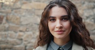 Close-upportret van het charmeren van meisje die camera glimlachen bekijken die zich in openlucht bevinden stock videobeelden