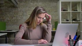 Close-upportret van het geconcentreerde vrouwelijke beambte typen op laptop die moeilijkheden hebben en een oplossing vinden stock video
