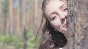 Close-upportret van het gelukkige het glimlachen jonge vrouw kijken van achter de boomboomstam en opnieuw het verbergen Eenheid m stock video